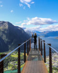 Panoramic view of woman taking photo of Andalsnes on a platform at the top of the mountain